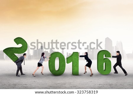 Image of business team work together to arrange numbers 2016 outdoors - stock photo