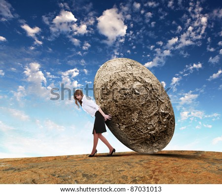 Image of business woman rolling a giant stone - stock photo