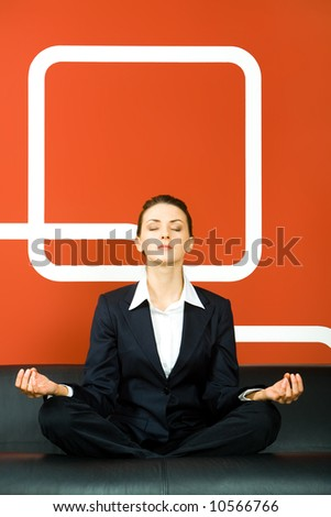 Image of business woman sitting on the sofa in pose of lotus - stock photo