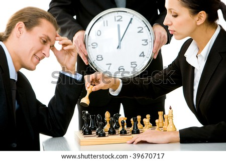 Image of businessman and businesswoman playing chess with businessman holding clock on background - stock photo