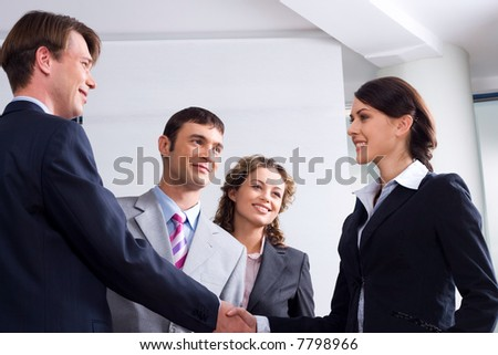Image of businessman and woman shaking hands at meeting - stock photo