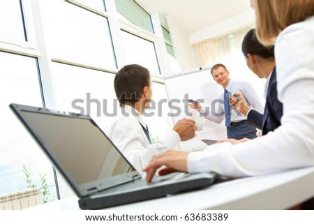 Image of businessman doing presentation to businesspeople during conference