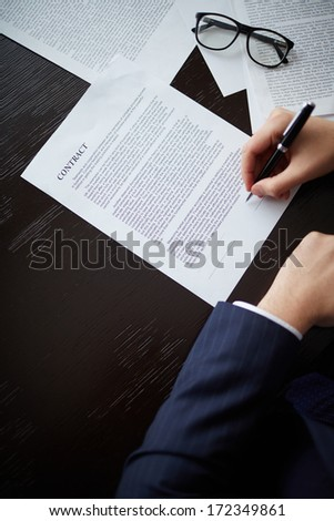 Image of businessman hand with pen signing contract at workplace - stock photo
