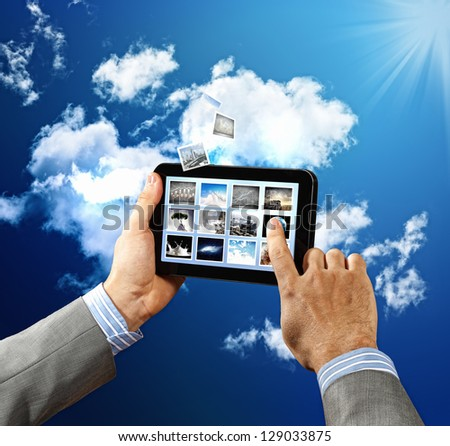 Image of businessman hands touching pad against sky background - stock photo