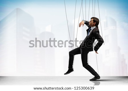 Image of businessman hanging on strings like marionette against city background. Conceptual photography - stock photo