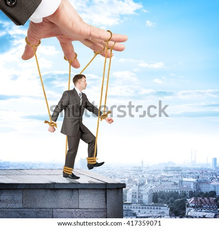 Image of businessman hanging on strings like marionette. Conceptual photography - stock photo