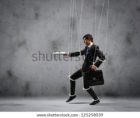 Image of businessman hanging on strings like marionette with briefcase in hand. Conceptual photography - stock photo
