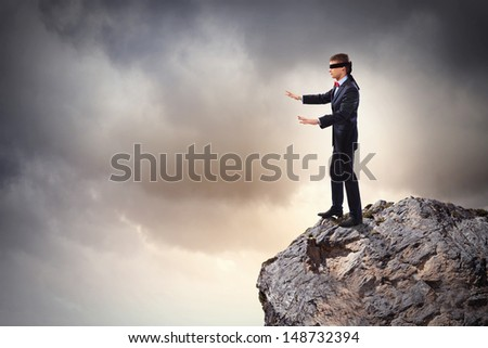 Image of businessman in blindfold standing on edge of mountain