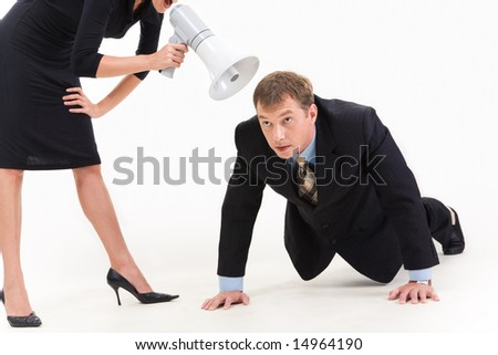 Image of businessman in suit doing physical exercise while standing woman shouting at him through loudspeaker - stock photo
