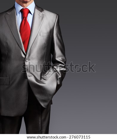 Image of businessman in suit over gray background with copyspace - stock photo