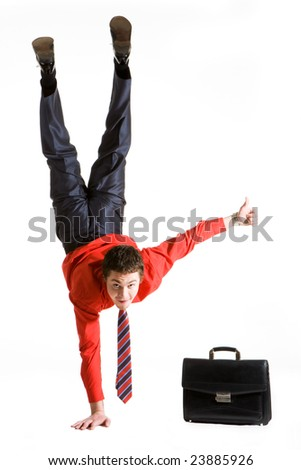 Image of businessman keeping himself on one arm while showing thumb up with another hand - stock photo