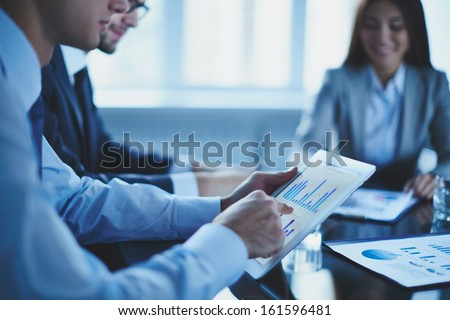 Image of businessman pointing at document in touchpad at meeting - stock photo