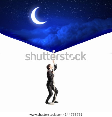 Image of businessman pulling banner with illustration. Day and night concept - stock photo
