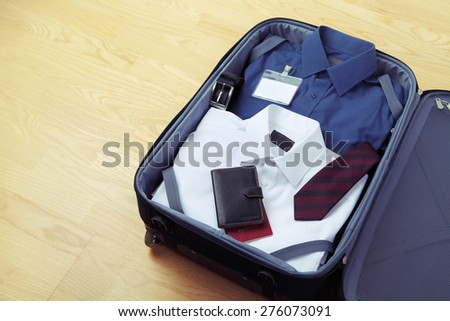 Image of businessman's clothes in travel bag - stock photo