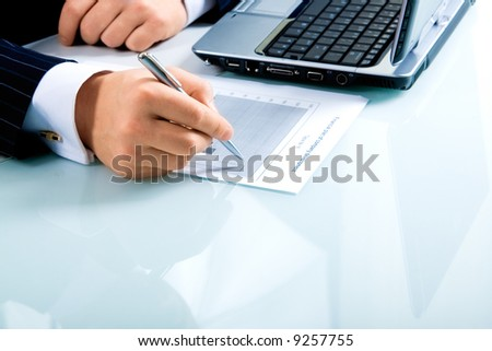 Image of businessman's hand ready to make notes in a document with laptop near by