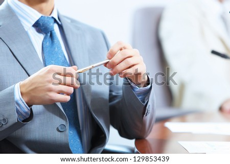 Image of businessman's hands laying on table with pen - stock photo