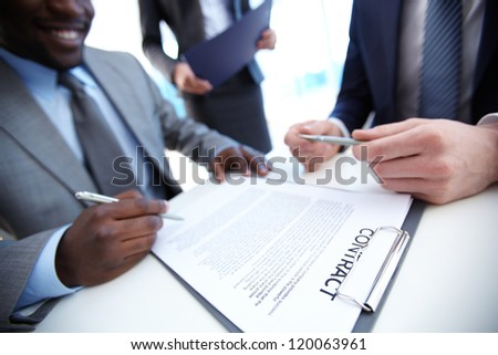 Image of businessman signing contract with two employees near by - stock photo