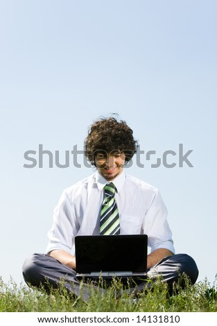 Image of businessman sitting in the pose of lotus and working on open air