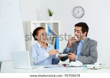 Image of businessman sneezing while his anxious partner giving him a cup of tea in office - stock photo