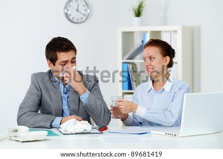 Image of businessman sneezing while his partner giving him tablets and water in office - stock photo