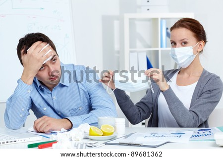 Image of businessman sneezing while his partner in mask offering him to put on one in office - stock photo