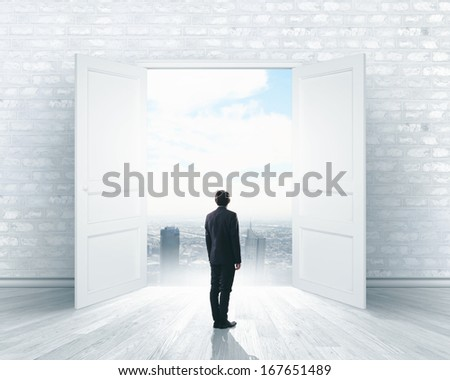 Image of businessman standing in front of opened door - stock photo