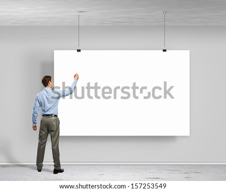 Image of businessman standing with back and writing on blank banner - stock photo