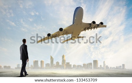 Image of businessman standing with back looking at airplane in sky - stock photo