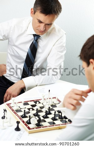 Image of businessman thinking while playing chess