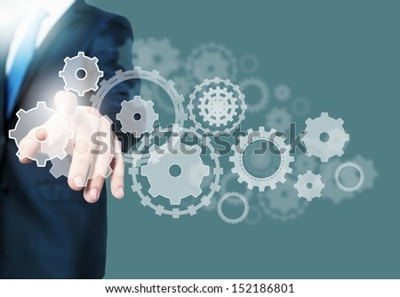 Image of businessman touching gear elements. Mechanism concept