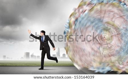 Image of businessman trying to run away from money rolling behind