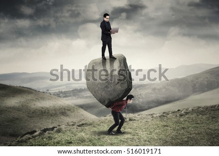 Image of businessman using a laptop and standing above a stone while his partner lifting a big stone on the hill