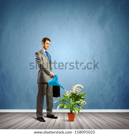 Image of businessman watering money tree with currency symbols - stock photo