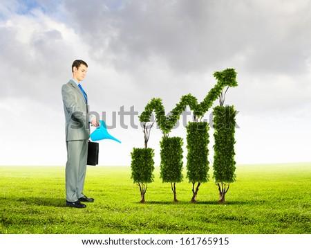 Image of businessman watering plant shaped like arrow - stock photo