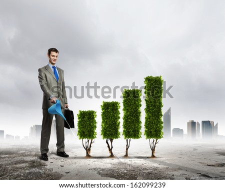Image of businessman watering plant shaped like graph - stock photo