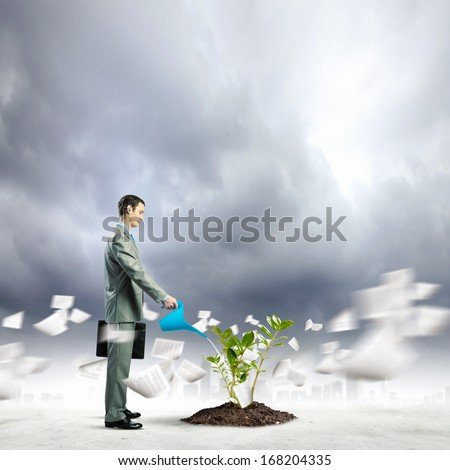 Image of businessman watering sprout with can