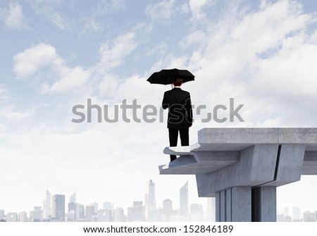 Image of businessman with umbrella standing at the edge of bridge