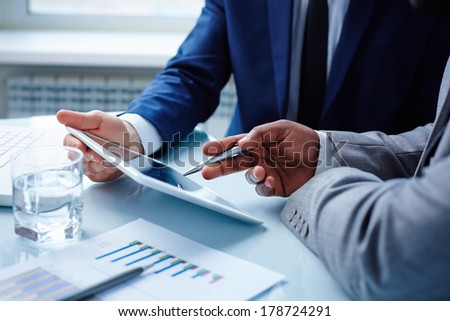 Image of businessmen discussing data in touchpad at meeting - stock photo