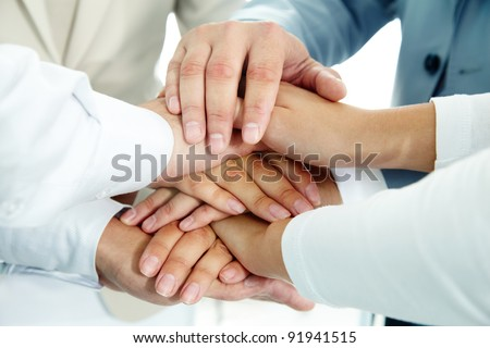 Image of businesspeople hands on top of each other as symbol of their partnership - stock photo