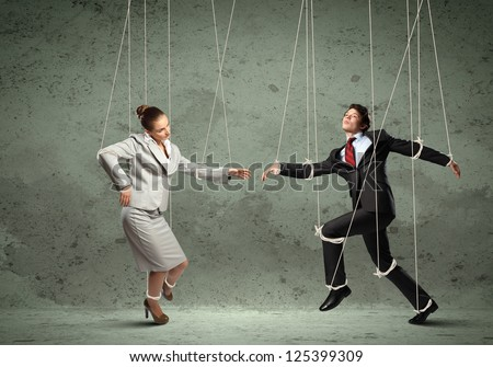 Image of businesspeople hanging on strings like marionettes. Conceptual photography - stock photo