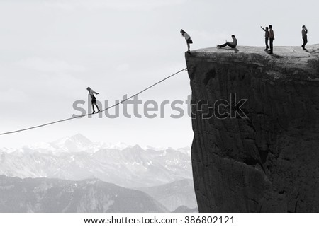 Image of businesspeople walking on the gap one by one with a rope - stock photo