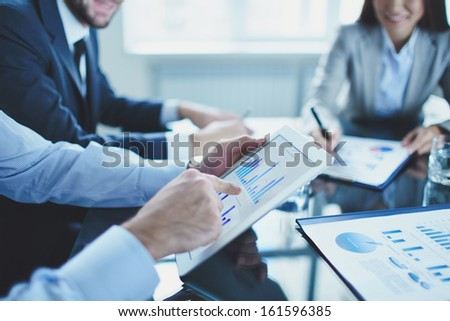 Image of businessperson pointing at document in touchpad at meeting - stock photo