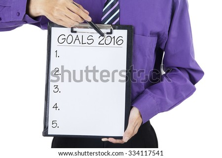 Image of businessperson with formal suit, holding a clipboard with a list of goals for 2016 - stock photo
