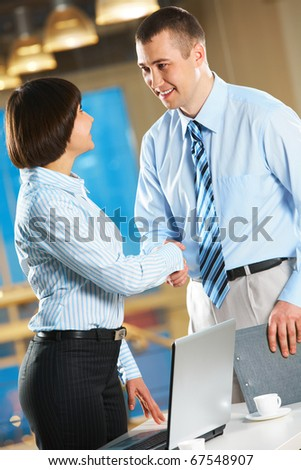 Image of businesswoman and businessman handshaking in the office - stock photo