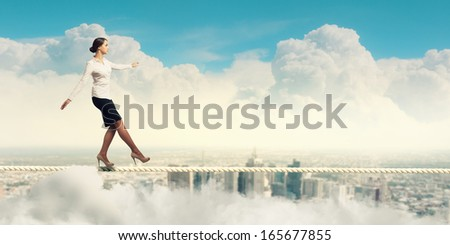 Image of businesswoman balancing on rope. Risk concept - stock photo