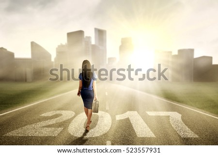 Image of businesswoman carrying a briefcase while walking towards to city with numbers 2017 and sunlight
