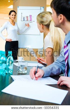 Image of businesswoman demonstrating her project to business partners at seminar - stock photo