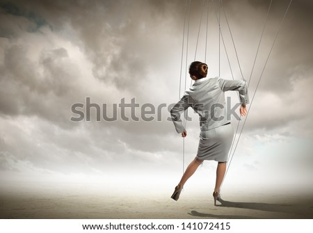 Image of businesswoman hanging on strings like marionette. Conceptual photography - stock photo