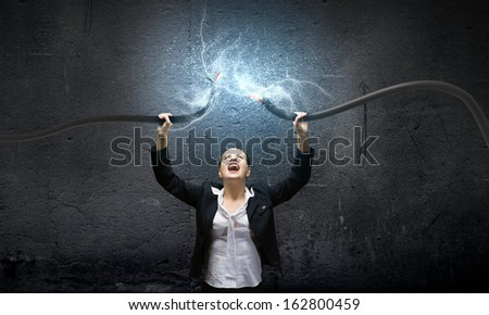 Image of businesswoman holding electrical cable above head - stock photo