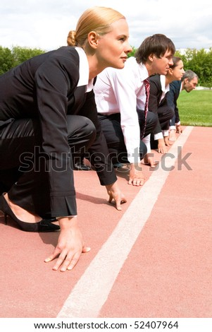 Image of businesswoman looking attentively forwards waiting for signal to run with partners on background - stock photo